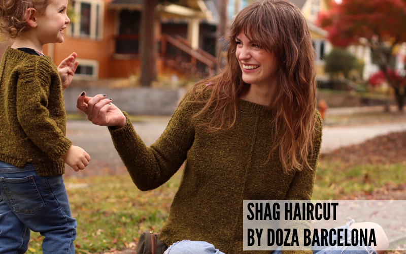 A stylish mom with a shag haircut playing with her son in matching sweaters. Haircut by Doza Barcelona.